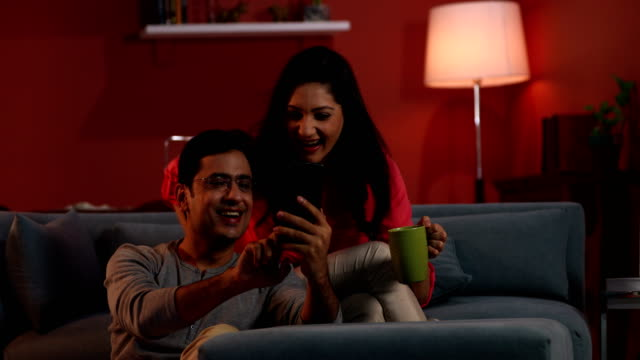 Couple chatting on mobile phone, Delhi, India