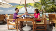 couple cheering with cocktails on tropical terrace