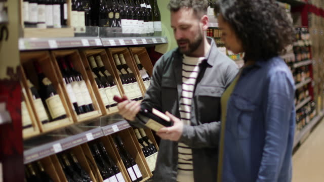 Couple choosing wine in grocery store