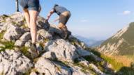 Couple climbing mountain ridge to summit