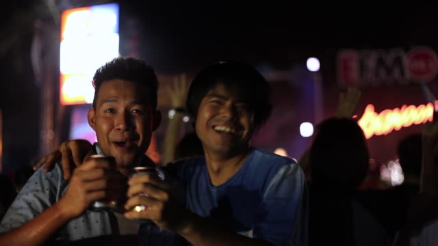 Couple close friend singing and dancing in the outdoor concert with drinking beer