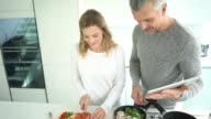 Couple cooking at home following a recipe