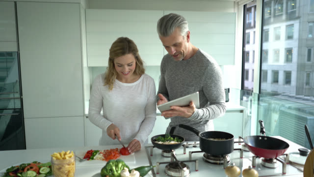 Couple cooking at home following an online recipe