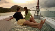 A couple cuddles as they sit on the netting of a catamaran.