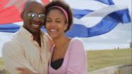 CU Couple cuddling, Cuban flag in background / Havana, Cuba