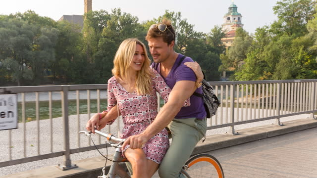 Couple cycling along river on one bicycle