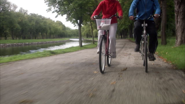 Couple cycling alongside a canal, Sweden.