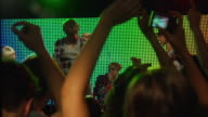 MS TD SLO MO Couple dancing and taking photograph at rock concert / London, UK