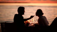 couple dining on beach at sunset