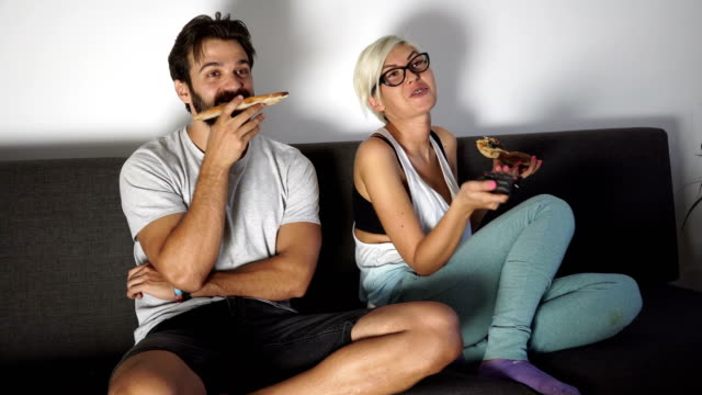 Couple dining pizza next to TV