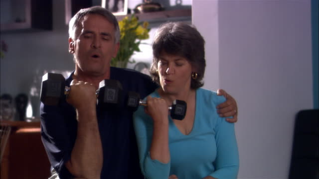 Couple doing arm curls with dumbbells inside home
