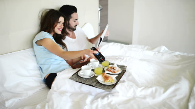 couple doing breakfast on the bed of hotel room