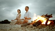 PAN Couple doing half lotus on beach by the fire