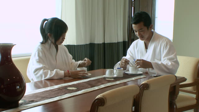 MS Couple drinking tea at table in hotel room / Sihanoukville, Cambodia