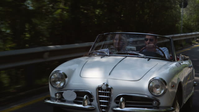 Couple driving cabriolet