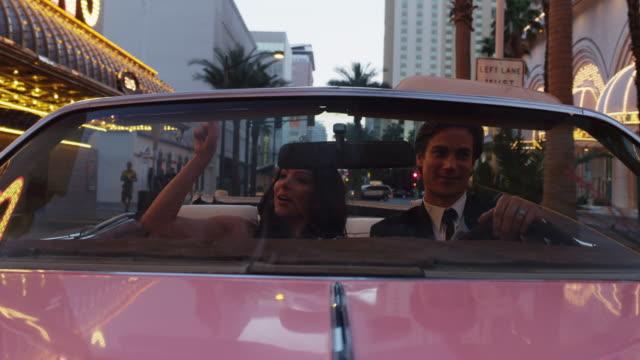 POV MS Couple driving through neon illuminated city street in convertible car / Las Vegas,Nevada,USA