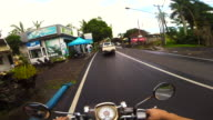 Couple during travel vacations in Bali recording road from personal perspective using action cam while riding motorbike in the Bali roads.