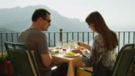 MS Couple eating at outdoor table on balcony / Ravello,Campania