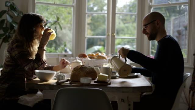 Couple eating breakfast in sunny kitchen