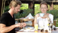 couple eating breakfast on tropical terrace