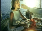 MS Couple eating dinner on terrace of restaurant next to water. They drink wine. Man puts cracker in woman's mouth / Bermuda