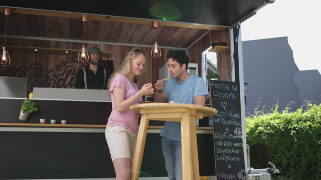 Couple eating outside at food truck