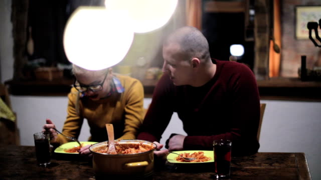 Couple eating pasta at home