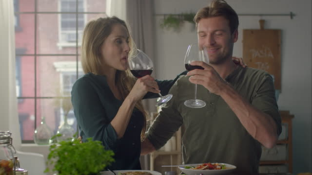 Couple eating self-made food and drinking wine in the kitchen
