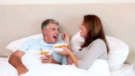 Couple eating while lying in bed