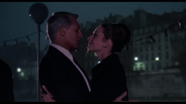Couple (Cary Grant and Audrey Hepburn) embrace and kiss as they travel along the River Seine at night