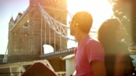 Couple enjoy sun in front of the Tower Bridge