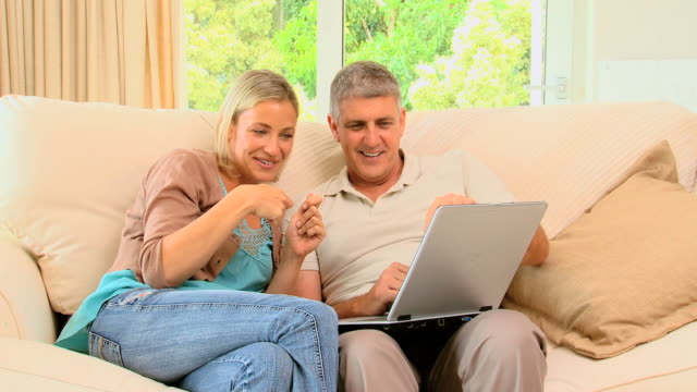 Couple enjoying pictures on laptop on sofa / Cape Town, Western Cape, South Africa