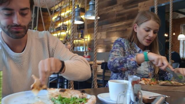 Paar genieten van pizza in pizzeria