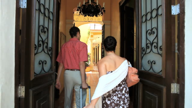 WS Couple entering hotel, being greeted by man, Merida, Yucatan, Mexico