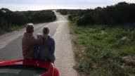 Couple exit car to look down long rural road