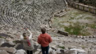 Couple explore from stone steps of ancient Greek amplitheatre