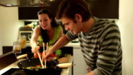 MS PAN  Couple fighting for eating best vegetables in wok with chopsticks / London, UK