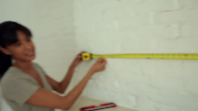 MS PAN Couple fixing up house interior, measuring wall with tape / Brooklyn, New York City, USA