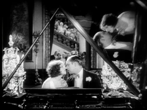 CU, B&W, Couple flirting at grand piano, people in background cheering, 1920's