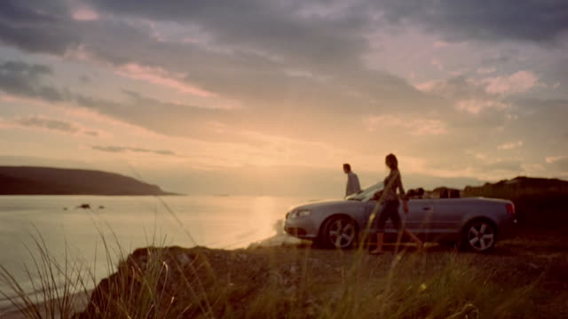 Couple getting out of convertible car parked on bluff at sunset / sitting down and looking at view of loch / Scotland