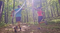 SLO MO TS Couple giving high five while running through the forest