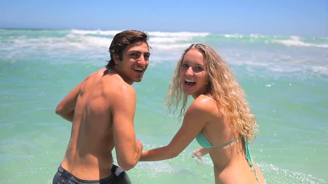 Couple going into the ocean