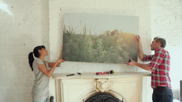 MS Couple hanging picture in living room / Brooklyn, New York City, USA