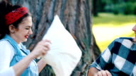 Couple have a pillow fight on a picnic slowmotion