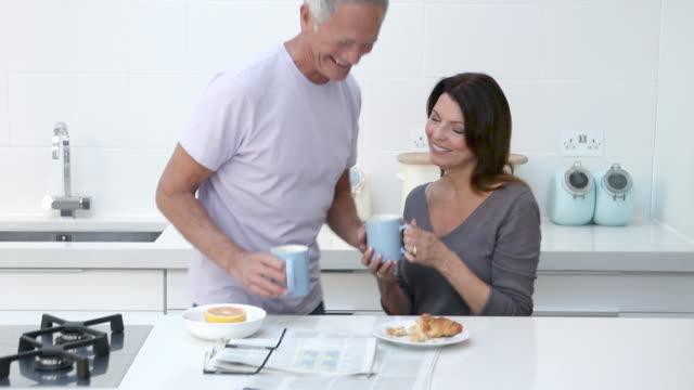Couple having breakfast with newspaper