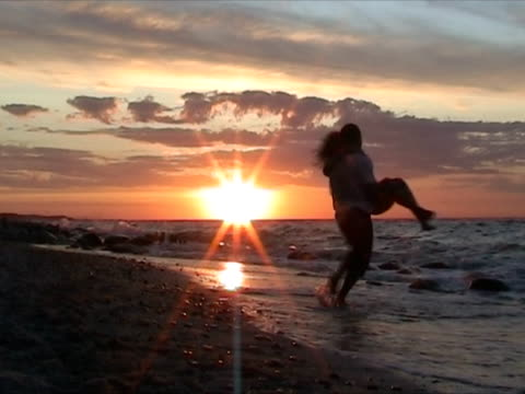 Couple having fun at the beach during sunset