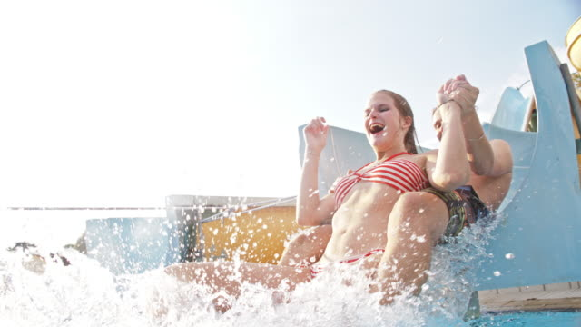 SLO MO Couple having fun on a water slide