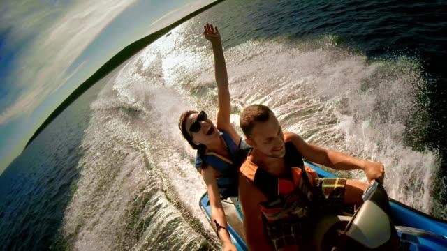 POV coppia divertendosi guida su una moto d'acqua