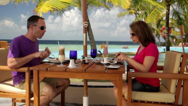 couple having lunch on a tropical beach terrace