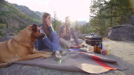 MS Couple having picnic on blanket at wilderness campsite while dog watches